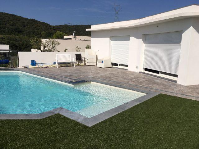 Illustration de l'intégration réussie du béton imprimé dans l'environnement - piscine, pool-house, gazon synthétique-