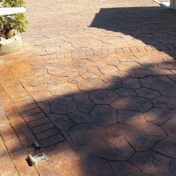 Jonction pavé droit / pavé irrégulier avec le début de la terrasse en arrière-plan. On visualise le système de fixation au sol du portail.