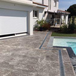 Autre vue de la terrasse terminée. Le caniveau suit les contours de la piscine pour un plus grand esthétisme.