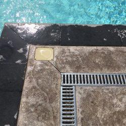Zoom sur le caniveau et le coffrage du regard rehaussé du point électrique du projecteur de piscine. La plage en béton imprimé est à fleur de margelle, à la demande du client.